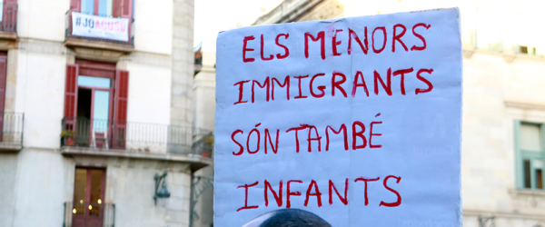 Cartell amb el missatge 'Els menors immigrants són també infants', en la concentració convocada per l'associació Ex-Menas a la plaça de Sant Jaume, el 16 de març del 2019. Foto: Laura Fíguls / ACN
