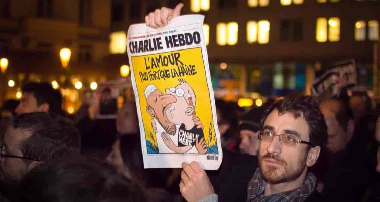 Un home mostra una portada de 'Charlie Hebdo' en una concentració de suport a la revista, a Brussel·les. Foto: Aurellen Guichard.