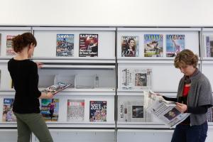 Dues dones llegeixen diaris i revistes a la Biblioteca de Navarcles. Foto: Diputació de Barcelona.