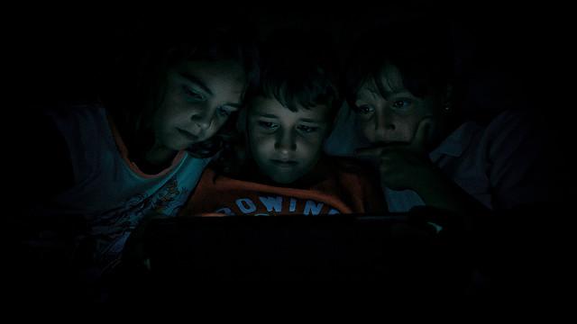 Tres infants observen la pantalla d'un dispositiu. Foto: Hernán Piñera.