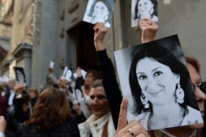 Assistents a la missa en memòria de Daphne Caruana Galizia als sis mesos del seu assassinat mostren fotografies de la seva cara.