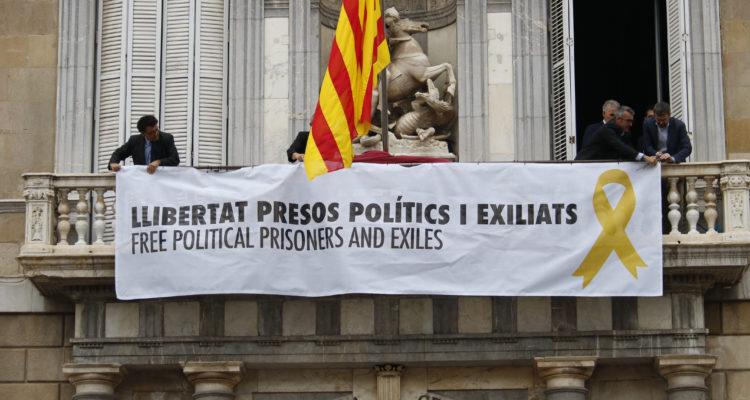 Treballadors del govern català pengen una pancarta amb el llaç groc al balcó del Palau de la Generalitat, el juny de 2018. Foto: Aleix Freixas / ACN.