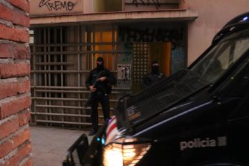 Dos agents i una furgona dels Mossos d'Esquadra custodiant un dels domicilis que s'estan registrant en el marc d'un operatiu policial el 15 de gener del 2019. Foto: Miquel Codolar / ACN.