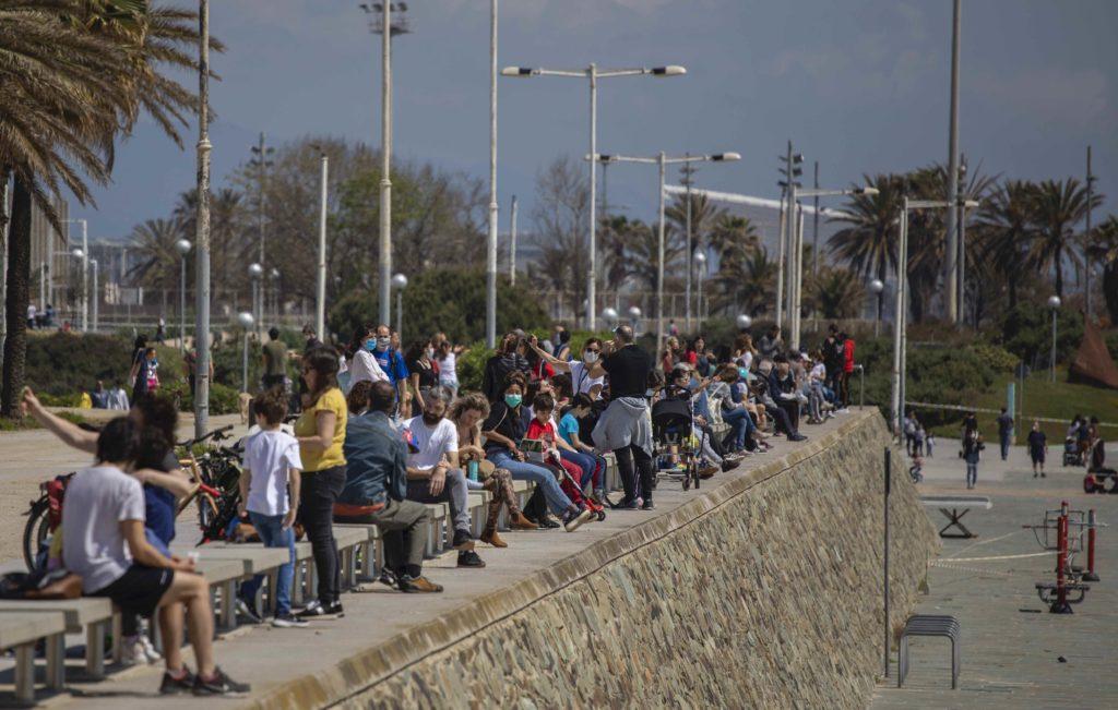 Les famílies amb els seus fills s'asseuen davant de la platja de Barcelona mentre la policia patrulla, on està prohibit l'accés el diumenge 26 d'abril de 2020. Foto: Emilio Morenatti / AP