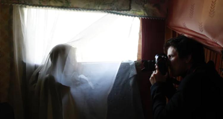 La fotògrafa Susana Vera fa fotos d'un nen mirant a través de la finestra de la seva barraca a l'antic assentament del Galliner als afores de Madrid. Foto: Carlos Rosillo