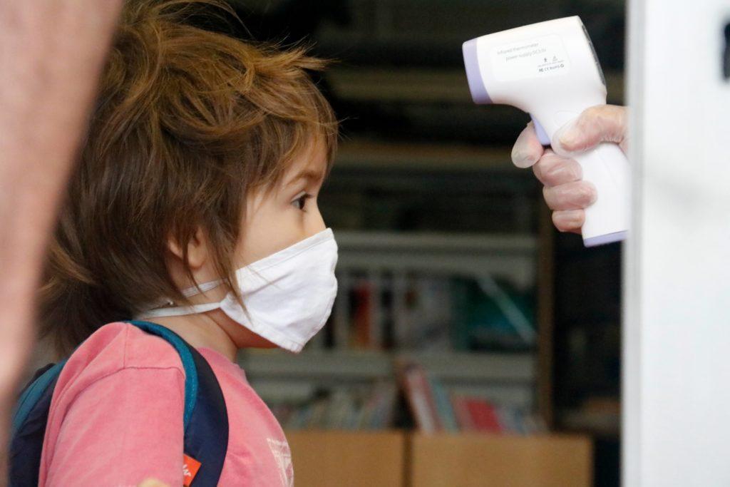 Prenen la temperatura a un alumne d'infantil a l'Institut Escola Costa i Llobera. Foto: Blanca Blay / ACN
