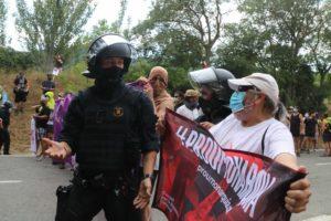 Un agent policial i un manifestant, encarant-se, en un moment de tensió en una protesta convocada en contra de la visita dels Reis d'Espanya al monestir de Poblet. Foto: Roger Segura / ACN