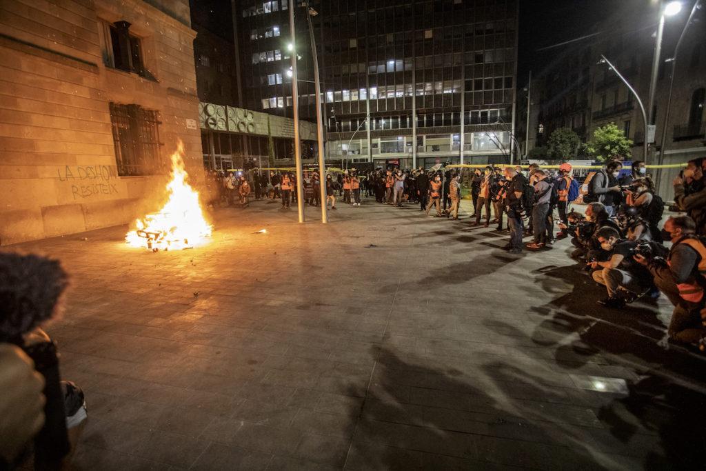 Fotògrafs i videògrafs capturen uns palets cremant, en la manifestació contra els desnonaments de l'octubre passat a Barcelona. Foto: Victor Serri (cedida).