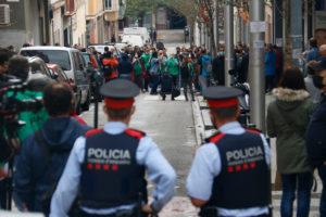 Dos agents dels Mossos miren cap als membres de la PAH concentrats arran d'un desnonament previst a Nou Barris, a Barcelona. Foto: Blanca Blay / ACN.