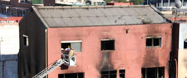 Els bombers recuperen aquest dijous el cos d'una víctima mortal en l'incendi de la nau a Badalona. Foto: Albert Segura Lorrio / ACN.