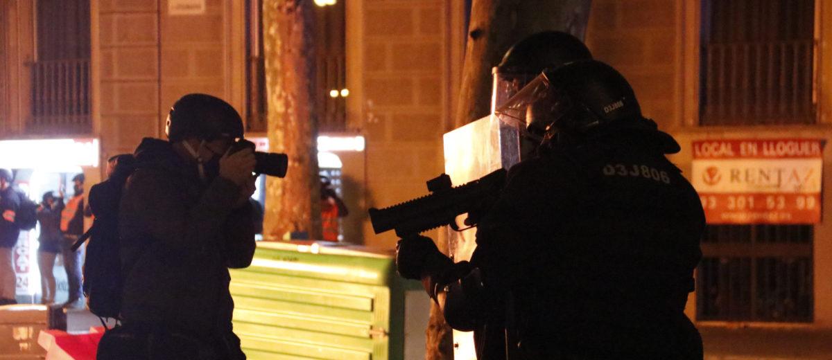 Un periodista fotografia uns agents dels Mossos d'Esquadra amb una llançadora de foam durant unes protestes per l'empresonament del cantant Pablo Hasel el 17 de febrer del 2021 a Barcelona. Foto: Blanca Blay / ACN.