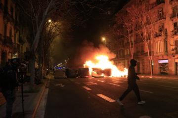 Una càmera grava com un manifestant passa pel davant d'una barricada de contenidors cremant a Barcelona. Foto: Laura Fíguls / ACN.