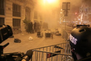 La premsa observa com agents de Mossos i de la Policia Nacional custodien la Prefectura mentre alguns manifestants tiren escombraries i petards, diumenge al vespre. Foto: Laura Fíguls / ACN.