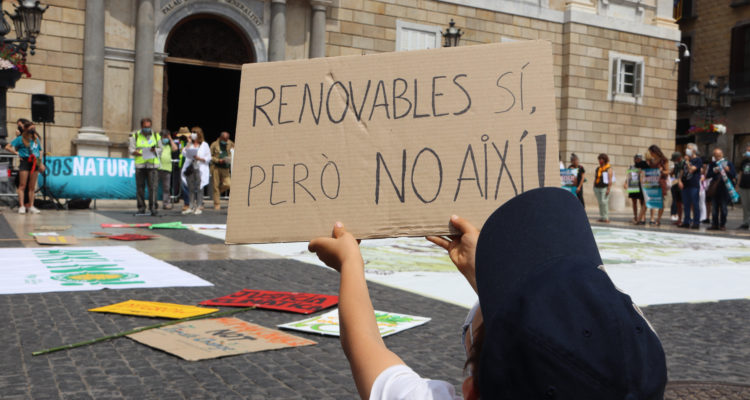 Un nen sosté un cartell on es llegeix 'Renovables sí, però així no', en la concentració del 5 de juny a Barcelona. Foto: Mar Martí / ACN.