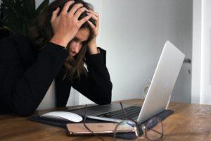 Una dona es posa les mans al cap davant l'ordinador. Foto: Unsplash. Elisa Ventur