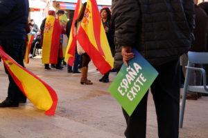 Primer pla d'un cartell d''España Existe' que sosté un simpatitzant de l'extrema dreta i banderes d'Espanya a una concentració de Vox. Foto: ACN/Anna Ferràs