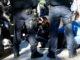 Dos agents dels Mossos, d'esquenes, amb activistes al terra que intenten evitar un desnonament. / Foto: ACN. Blanca Blay