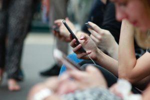 Diverses persones mirant el mòbil. Foto: Unsplash. Robin Worrall